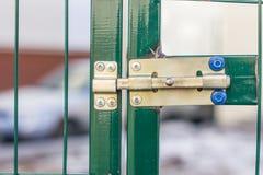 Gelber Verschluss auf grüner Tür Zaun um den Garten Lizenzfreie Stockfotos