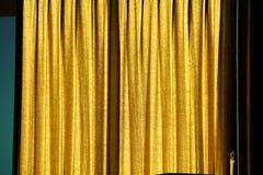 Gelber Vorhang auf Fenster Stockfotos
