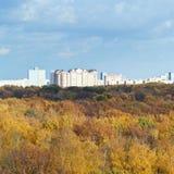 Gelber Wald, städtische Häuser, blaue Wolken Stockfotos