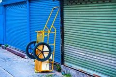 Gelber Warenkorb lokalisiert ` an der blauen Rollentür Lizenzfreie Stockbilder