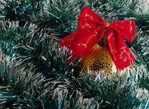 Gelber Weihnachtsball mit rotem Bogen im grünen Lametta Lizenzfreie Stockbilder
