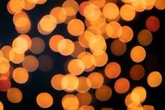 Gelber Weihnachtsbaum Bokeh auf schwarzem Hintergrund von defocused funkelnden Lichtern, Weihnachtshintergrund-Musterkonzept lizenzfreie stockbilder