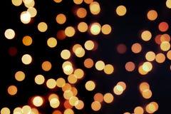 Gelber Weihnachtsbaum Bokeh auf schwarzem Hintergrund von defocused funkelnden Lichtern, Weihnachtshintergrund-Musterkonzept stockfotografie