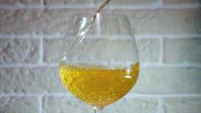 Gelber Wein, der in Glas in der Zeitlupe gießt stock video footage