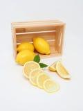 Gelber Zitronen- und Holzkasten Stockbilder