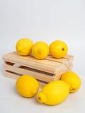 Gelber Zitronen- und Holzkasten Stockfotos