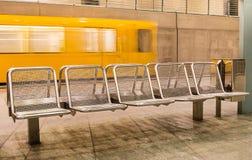 Gelber Zug, der hinter Metallsitze beschleunigt lizenzfreie stockfotografie