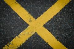 Gelbes x-Überfahrtzeichen gemalt auf dem Straßenasphalt Lizenzfreie Stockfotos