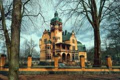Gelbes altes Haus mit Drehköpfen und einem Zaun, Schweden stockfotos