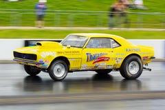 Gelbes amerikanisches Muskelauto auf einem Luftwiderstandstreifen Stockfotos
