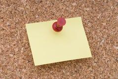 Gelbes Anmerkungs-Papier mit Heftzwecke auf Korken-Oberfläche Stockfoto