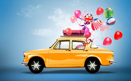 Gelbes Auto mit Symbolen der Liebe, des Feiertags, des happyness und der Reise. Stockfotos
