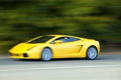 Gelbes Autoauf Landstraße schnell fahren Stockbild