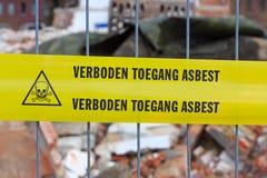 Gelbes Band auf Zaun mit niederländischem Text 'kein Eintrittsasbest' Stockbild