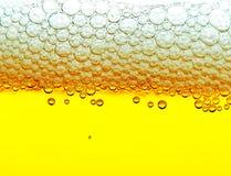 Gelbes Bier mit Schaumgummi und Luftblasen stockfotos