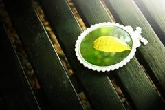 Gelbes Blatt auf dem Spiegel Stockbild