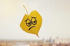 Gelbes Blatt mit einem Bild eines traurigen Gesichtes Stockbild