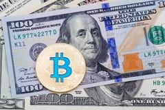 Gelbes blaues bitcoin auf hundert Banknotenhintergrund Stockfotografie