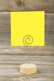 Gelbes Briefpapier auf einem Halter auf grauem hölzernem Hintergrund Stockbild