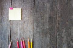 Gelbes Briefpapier auf hölzernem Hintergrund mit farbigen Bleistiften Stockfotografie