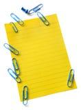 Gelbes Briefpapier mit Papierklammern Stockbilder
