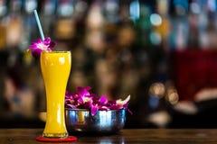 Gelbes Cocktail mit Orchideenblume in der Bar Stockfoto