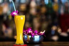 Gelbes Cocktail mit Orchideenblume in der Bar Stockfotos
