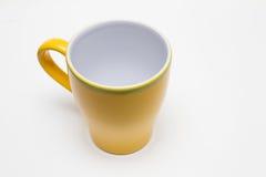 Gelbes Cup auf weißem Hintergrund Stockbild