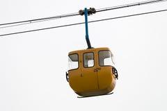 Gelbes Drahtseilbahnhängen Lizenzfreie Stockfotografie