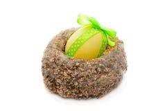 Gelbes Ei verziert mit Farbband in einem Nest Stockfoto