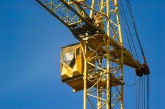 Gelbes Fahrerhaus eines Baus, der Kran hochzieht Stockfotos