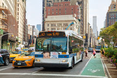 Gelbes Fahrerhaus und Bus an der 5. Allee morgens Lizenzfreie Stockfotos