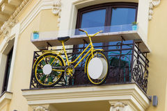 Gelbes Fahrrad auf einem Balkon Stockbilder