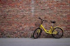 Gelbes Fahrrad durch die Wand des roten Backsteins Lizenzfreies Stockbild