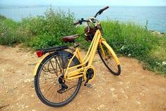Gelbes Fahrrad nahe dem Meer Stockfotografie