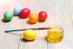 Gelbes Farbenglas mit Malerpinsel auf hölzernem Hintergrund, Ostereier Stockbild