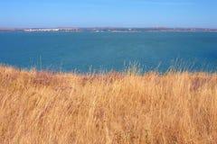 Gelbes Feld des trockenen Grases, blaues Meer und Himmel, Krim Stockfoto