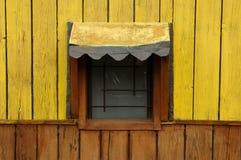 Gelbes Fenster eines hölzernen Häuschens Stockfotografie