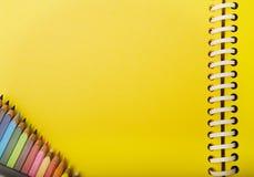 Gelbes Frühlingsnotizbuch und -zeichenstifte in einer Ecke. Lizenzfreie Stockbilder