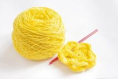 Gelbes Garn und eine Häkelarbeitblume stockfoto