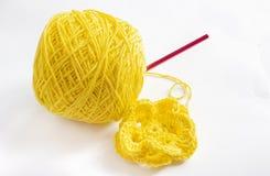 Gelbes Garn und eine Häkelarbeitblume lizenzfreies stockfoto