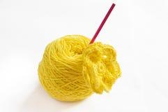 Gelbes Garn und eine Häkelarbeitblume Lizenzfreie Stockbilder
