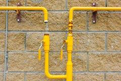 Gelbes Gasrohr auf der Wand, angeschlossen dem Gas an es Neues Haus, Stockfotos