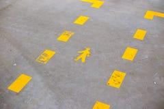 Gelbes gemaltes Zeichen, das Fußgängerwege anzeigt stockfotos