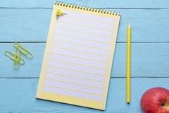 Gelbes gewundenes Notizbuch und ein Apfel auf einem blauen Schreibtisch lizenzfreie stockbilder