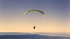 Gelbes Gleitschirmfliegen auf Pastellhimmel Lizenzfreies Stockbild