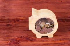 Gelbes hölzernes Sparschwein mit Münzen des russischen Rubels auf rotem hölzernem lizenzfreie stockfotos