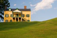 Gelbes Haus auf grasartigem Hügel Stockbild