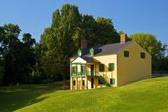 Gelbes Haus auf grasartigem Hügel Stockbilder