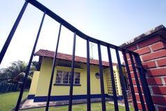 Gelbes Haus hinter Gatter des bearbeiteten Eisens Stockfoto
